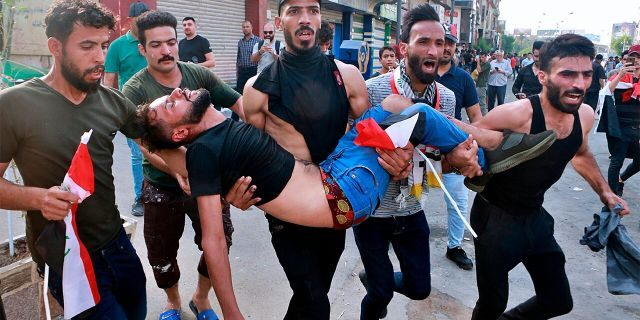 An injured protester being carried after reacting to tear gas fired by security forces during a protest in Tahrir Square, in central Baghdad, last Tuesday. (AP Photo/Khalid Mohammed)