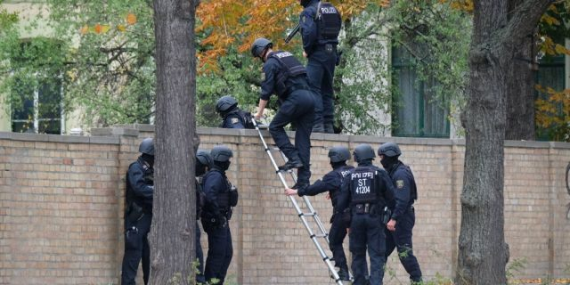 Police officers pictured here crossing a wall at a crime scene in Halle, Germany on Wednesday.