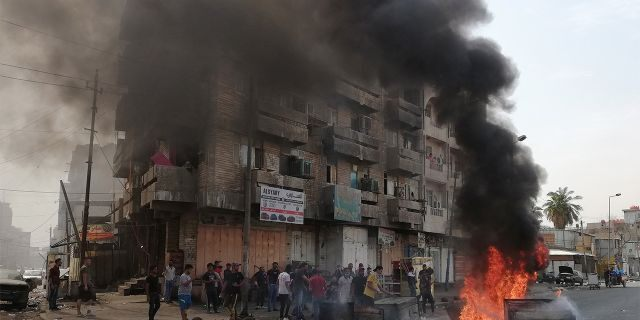 Anti-government protesters setting a fire and blocking roads in Baghdad last Wednesday. (AP Photo/Hadi Mizban)