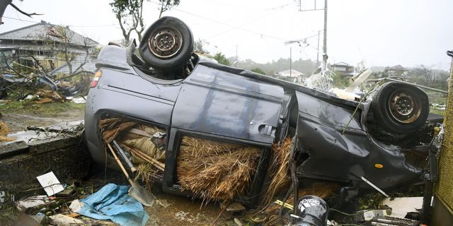 An overturned car lies on the ground following a strong wind in Ichihara, Chiba, near Tokyo Saturday, Oct. 12, 2019. Under gloomy skies, a tornado ripped through Chiba on Saturday.(Kyodo News via AP)