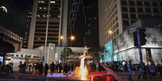 Demonstrators gather near a burning barricade in the street during a protest in Hong Kong, Saturday, Nov. 2, 2019. Anti-government protesters attacked the Hong Kong office of China's official Xinhua News Agency for the first time Saturday after chaos broke out downtown, with police and demonstrators trading gasoline bombs and tear gas as the protest movement approached the five-month mark.