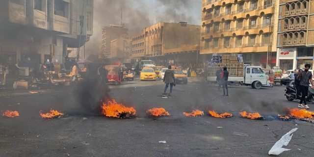 Anti-government protesters set fire to block streets during ongoing protests in Baghdad on Wednesday. (AP Photo/Ali Abdul Hassan)