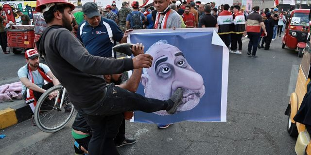 In this Sunday, Nov. 3, 2019 file photo, protesters hit a poster showing Iraqi Prime Minister Adel Abdel-Mahdi with shoes during ongoing anti-government protests in Baghdad. (AP Photo/Khalid Mohammed, File)