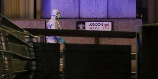 A police forensic officer walked by a sign where a man was shot dead by police on London Bridge on Friday. (AP Photo/Matt Dunham)