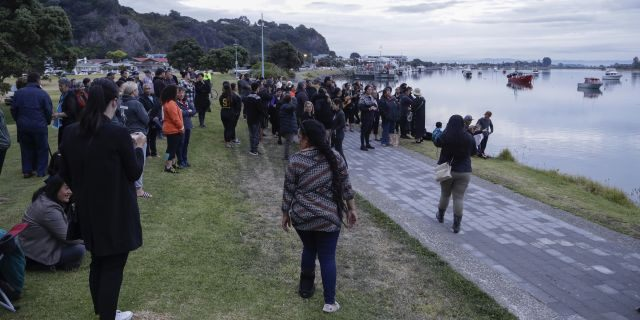 Locals sing during sunrise as they wait for the return of the victims after the White Island eruption to be returned to Whakatane, New Zealand, Friday, Dec. 13, 2019.