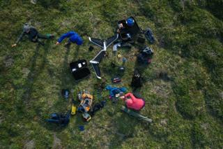 An aerial view of scientists working on a drone