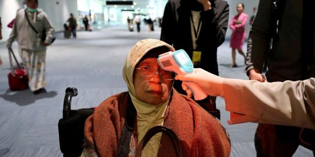 A health official scans the body temperature of a passenger as she arrives at the Soekarno-Hatta International Airport in Tangerang, Indonesia, Wednesday, Jan. 22, 2020. Indonesia is screening travelers from overseas for a new type of coronavirus as fears spread about a mysterious infectious disease after its first death reported in China. (AP Photo/Tatan Syuflana)