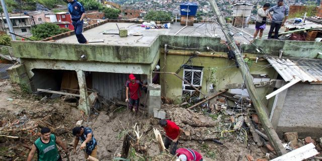 Locals work to clean up mud and debris around houses destroyed by a landslide after heavy rains in Vila Ideal neighborhood, Ibirite municipality, Minas Gerias state, Brazil.