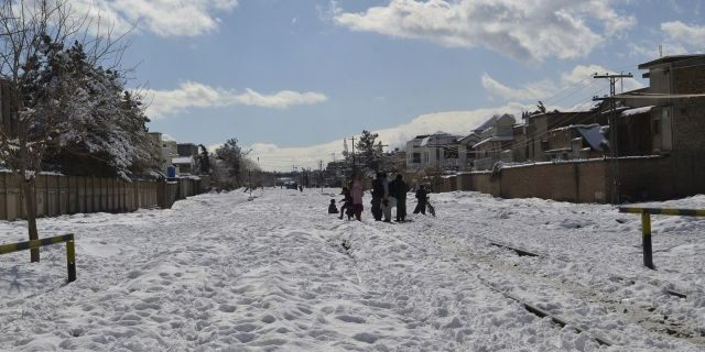 People walk on a railroad track covered with heavy snow in Quetta, capital of Pakistan's southwestern Baluchistan province on Monday.