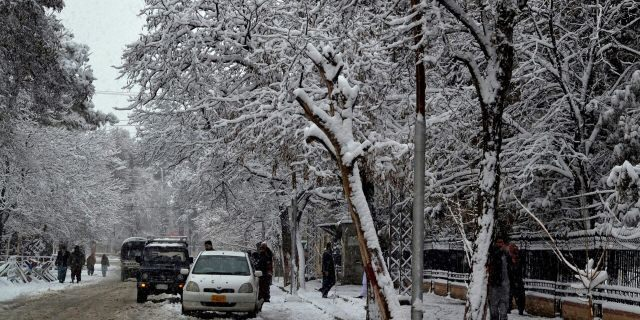 In this Sunday, Jan. 12, 2020, photo, people walk on a road during heavy snow fall in Quetta, capital of Pakistan's southwestern Baluchistan province.