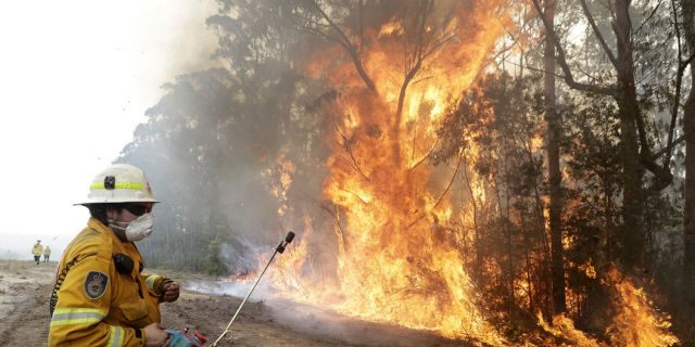 A firefighters backs away from the flames after lighting a controlled burn near Tomerong, Australia, Wednesday, Jan. 8, 2020, in an effort to contain a larger fire nearby.
