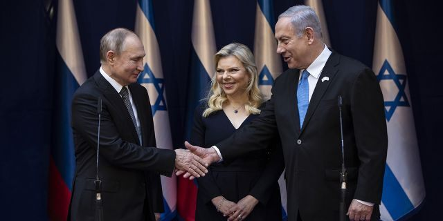 Israeli Prime Minister Benjamin Netanyahu and his wife Sarah meet with Russian President Vladimir Putin, left, at Netanyahu official residence in Jerusalem on Thursday, Jan. 23, 2020. Putin will be a guest of honor Thursday at a ceremony at the Yad Vashem Holocaust Museum marking the 75th anniversary of the Soviet Red Army's liberation of the Nazi Auschwitz death camp. (Heidi Levine/Pool photo via AP)