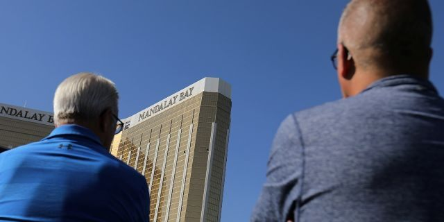 Tourists look up at the broken windows on the Mandalay Bay hotel where shooter Stephen Paddock conducted his mass shooting along the Las Vegas Strip in Las Vegas, Nev., October 4, 2017. (Reuters)