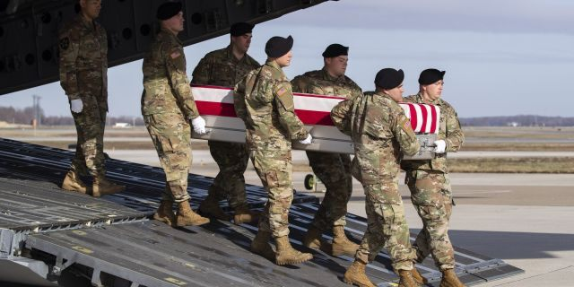 In this Dec. 25, 2019, file photo, an Army carry team moves a transfer case containing the remains of U.S. Army Sgt. 1st Class Michael Goble, at Dover Air Force Base, Del.