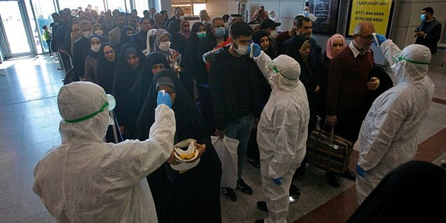 Friday, Feb. 21, 2020: Medical staff check passengers arriving from Iran in the airport in Najaf, Iraq. Coronavirus-infected travelers from Iran already have been discovered in Lebanon and Canada.