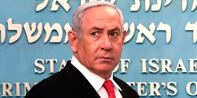 Prime Minister Benjamin Netanyahu approaches the podium to speak from his Jerusalem office on Saturday, March 14, 2020, saying Israel's restaurants and places of entertainment will be closed to stop the spread of the coronavirus.  (Gali Tibbon/Pool via AP)