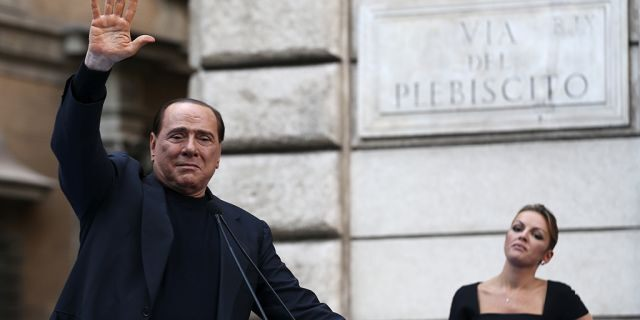 Former Italian Prime Minister Silvio Berlusconi waves to supporters as his girlfriend Francesca Pascale looks on during a rally to protest his tax fraud conviction, outside his palace in central Rome August 4, 2013. Tensions in Italy's squabbling coalition heightened ahead of a rally by supporters of Silvio Berlusconi in Rome on Sunday in protest at a tax fraud conviction that threatens his future in politics and the fragile government. REUTERS/Alessandro Bianchi (ITALY - Tags: POLITICS CIVIL UNREST) - GM1E98503SQ01