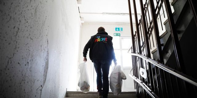 Pastor Bernd Siggelkow founder of the Christian charity the Arche, or Ark, carries bags with donated goods for poor families up the stairs of a center of the organization in Berlin, Germany, Tuesday, March 31, 2020. (AP Photo/Markus Schreiber)