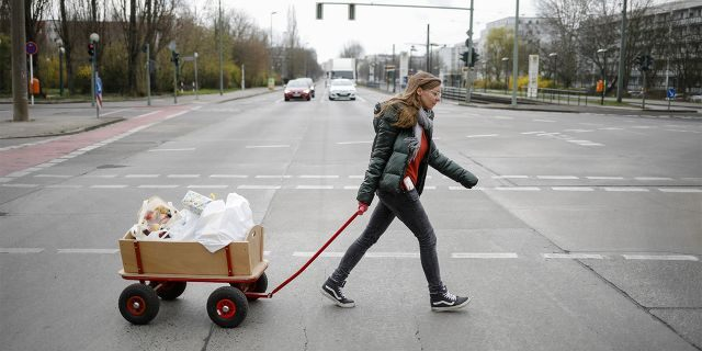 Social worker Rebekka Rauchhaus of the Christian charity the Arche, or Ark, pulls a cart as she walks through the district Hellersdorf to deliver food, toys and hygiene products to poor families in the Hellersdorf suburb of Berlin, Germany, Thursday. (AP Photo/Markus Schreiber)