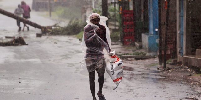 A man covers himself with a plastic sheet and walks in the rain ahead of Cyclone Amphan landfall, at Bhadrak district, in the eastern Indian state of Orissa, Wednesday, May 20, 2020.