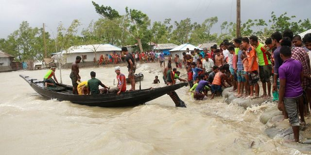 In this Wednesday, May 20, 2020 photo, a boat brings people to land, as locals check an embankment before Cyclone Amphan made landfall, in Shyamnagar, Shatkhira, Bangladesh.