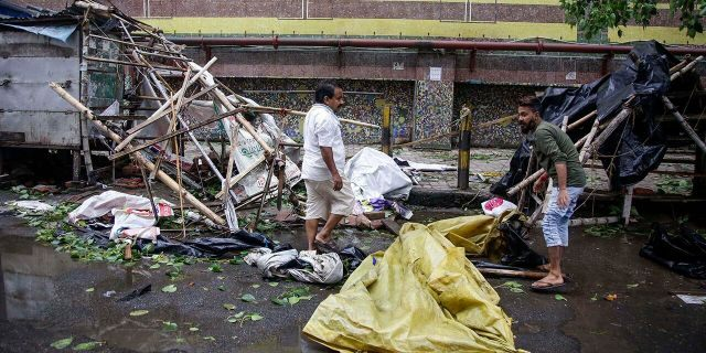 Roadside vendors along a metro station salvage material from his stall after Cyclone Amphan hit the region in Kolkata, India, Thursday, May 21, 2020. A powerful cyclone ripped through densely populated coastal India and Bangladesh.