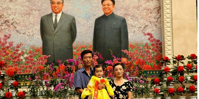 North Koreans pose for a family portrait in front of portraits of President Kim Il Sung (L) and his son Kim Jong Il. (Photo by Alain Nogues/Corbis via Getty Images)