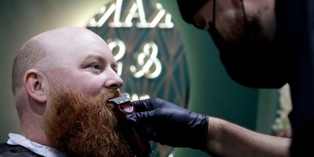 A man has his beard trimmed at a barber in Christchurch, New Zealand, Thursday, May 14, 2020. New Zealand lifted most of its remaining lockdown restrictions from midnight Wednesday (noon Wed GMT) as the country prepares for a new normal. Malls, retail stores and restaurants will reopen and many people will return to their workplaces.