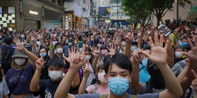 """Protesters against the new national security law gesture with five fingers, signifying the """"Five demands - not one less"""" on the anniversary of Hong Kong's handover to China from Britain in Hong Kong, Wednesday, July. 1, 2020. Hong Kong marked the 23rd anniversary of its handover to China in 1997, and just one day after China enacted a national security law that cracks down on protests in the territory"""