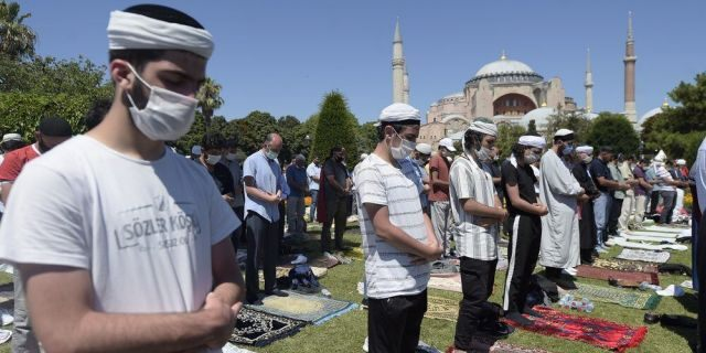 Muslims pray during Friday prayers at the historic Sultanahmet district of Istanbul, near the Byzantine-era Hagia Sophia, background, Friday, July 24, 2020.