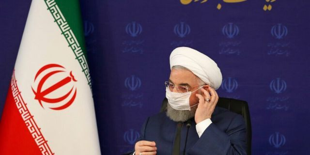 In this photo released by the official website of the office of the Iranian Presidency, President Hassan Rouhani adjusts his face mask in a meeting of the national headquarters of the fight against the COVID-19, in Tehran, Iran, Saturday, July 18, 2020. (Iranian Presidency Office via AP)