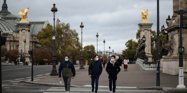 People wearing masks, walk in the Invalides district of Paris, Sunday, Oct.25, 2020. (AP Photo/Lewis Joly)