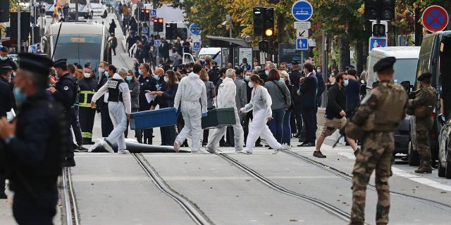 Forensics officers deploy stretchers at the site of a knife attack as French soldiers stand guard the street in Nice on Oct. 29, 2020. (Photo by VALERY HACHE/AFP via Getty Images)