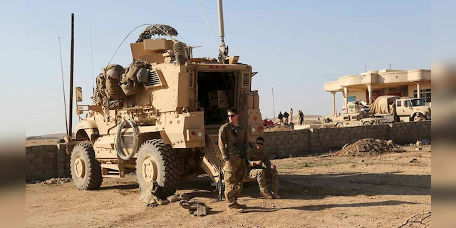 In this Feb. 23, 2017 file photo, U.S. Army soldiers stand outside their armored vehicle on a joint base with the Iraqi army, south of Mosul, Iraq. In a quest to root out Islamic State group hideouts over the summer, Iraqi forces on the ground cleared nearly 90 villages across a notoriously unruly northern province. But the much-touted operation still relied heavily on U.S. intelligence, coalition flights and planning assistance. (AP Photo/ Khalid Mohammed, File)