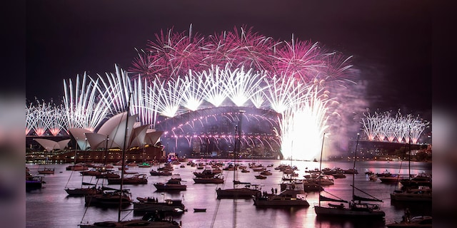 Fireworks explode over the Sydney Opera House and Harbour Bridge as New Year celebrations begin in Sydney, Australia, Friday, Jan. 1, 2021. Authorities advised revelers to watch the fireworks on television this year as the two most populous states, New South Wales and Victoria battle to curb new COVID-19 outbreaks. (AP Photo/Mark Baker)