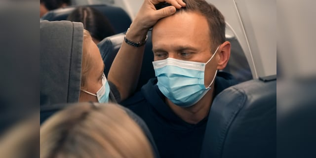 Alexei Navalny and his wife Yulia sit on the plane on a flight to Moscow, at the Airport Berlin Brandenburg (BER) in Schoenefeld, near Berlin, Germany, Sunday, Jan. 17, 2021.