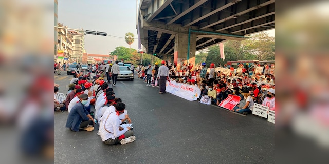 Anti-coup protesters gather under an elevated roadway just outside the Hledan Centre in Yangon, Burma Monday, Feb. 22, 2021. A call for a Monday general strike by demonstrators in Burma protesting the military's seizure of power has been met by the ruling junta with a thinly veiled threat to use lethal force, raising the possibility of major clashes. (AP Photos)