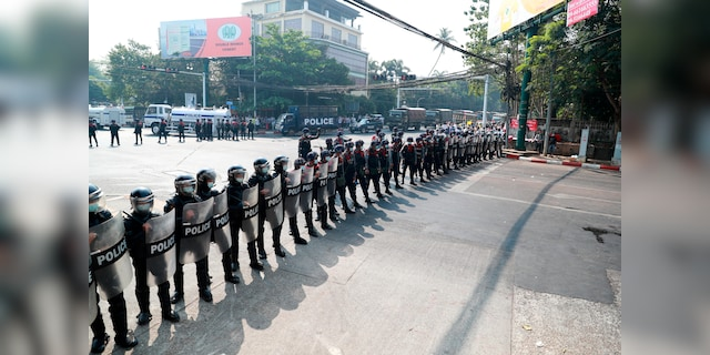 Police security forces form a line to block a road near the U.S. embassy in Yangon, Burma Monday, Feb. 22, 2021. Protesters gathered in Burma's biggest city Monday despite the ruling junta's thinly veiled threat to use lethal force if people answered a call for a general strike opposing the military takeover three weeks ago. (AP Photo)