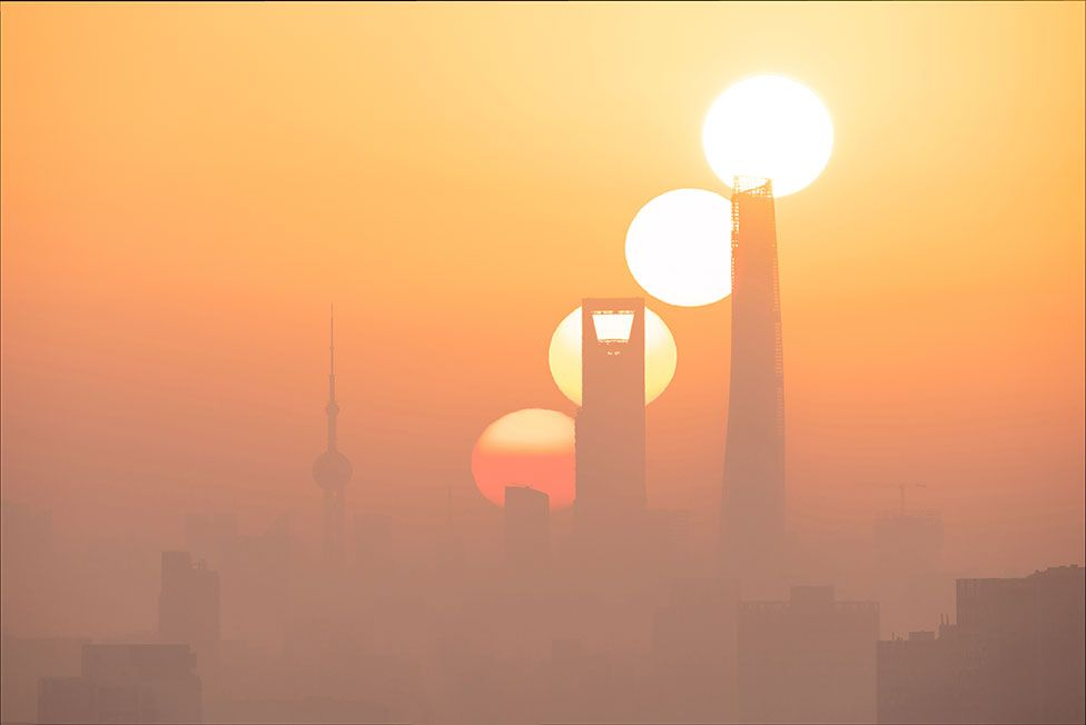 An image of the sun at different stages of a sunrise over Shanghai